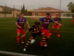 Perello's new centre forward holds off two Alcanar defenders